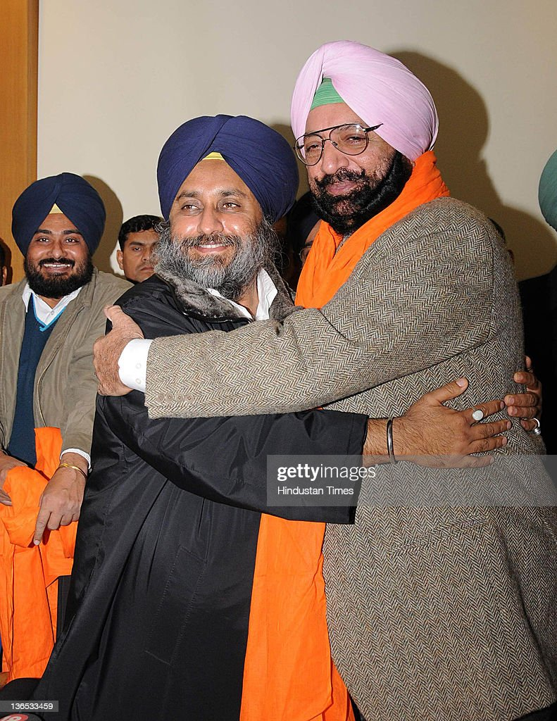 Sukhbir Singh Badal Deputy Chief Minister of Punjab hugging Malwinder Singh younger brother of State Congress Chief Capt Amrinder Singh during press..