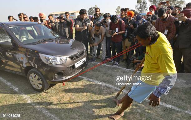 Sukhwinder Singh showing the strength by pulling a car with his teeth on the 2nd day of the 82nd Kila Raipur Rural Olympics 2018 in the village Kila...