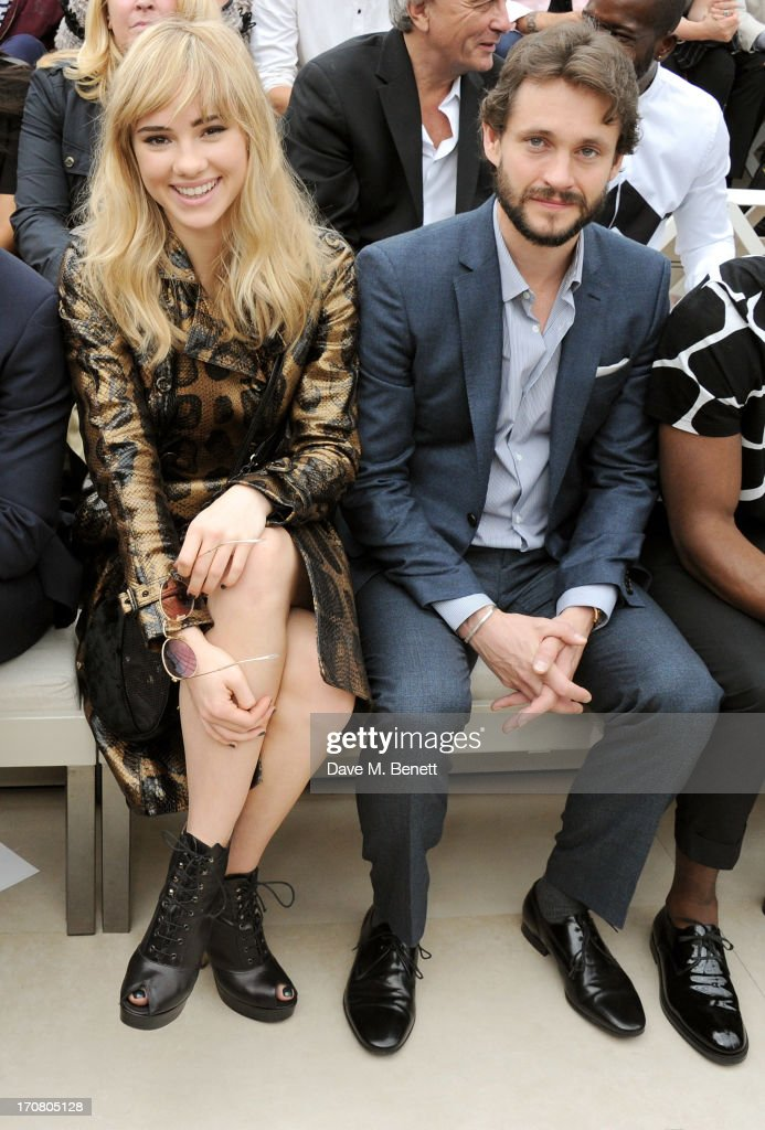 Suki Waterhouse (L) and Hugh Dancy sit in the front row at Burberry Menswear Spring/Summer 2014 at Kensington Gardens on June 18, 2013 in London, England.