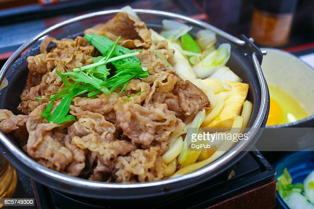 Sukiyaki served in hot pot with raw egg