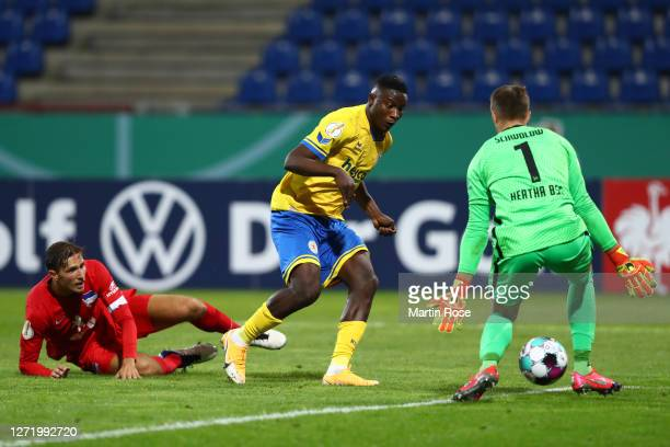 Suleiman Abdullahi of Eintracht Braunschweig scores his team's fifth goal past Alexander Schwolow of Hertha Berlin during the DFB Cup first round...