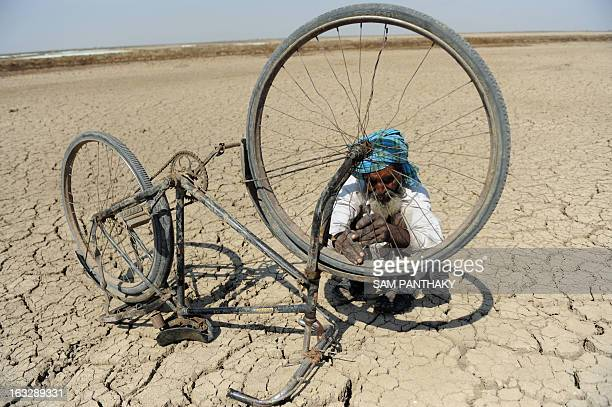 Sulemanbhai Sandhi an Indian salt flat worker repairs a bicycle in the Santalpur region of Little Rann of Kutch some 240 kms from Ahmedabad on March...