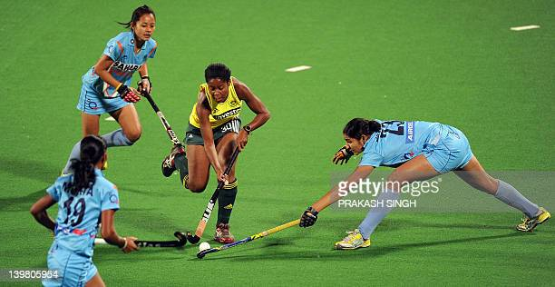 Sulette Damons of South Africa dribbles past Mukta Prava Barla and Jaspreet Kaur of India during the women's field hockey match between India and...
