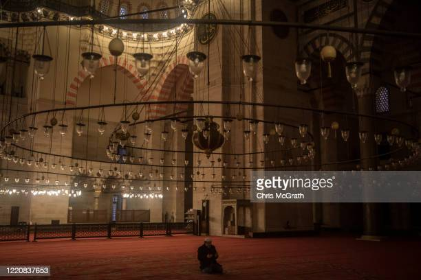 Suleymaniye Mosque Muezzin Davut Avci prays alone during the evening prayer in the closed Suleymaniye Mosque on the first day of the holy fasting...