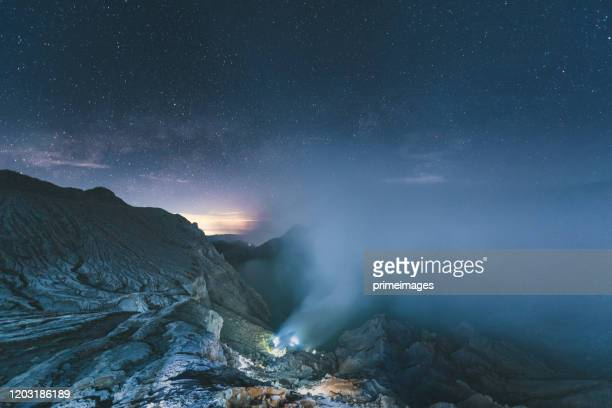 sulfur lake and smoking mine mountain in the morning at kawah ijen volcano east java indonesia with milky way night sky background - mt bromo stock pictures, royalty-free photos & images