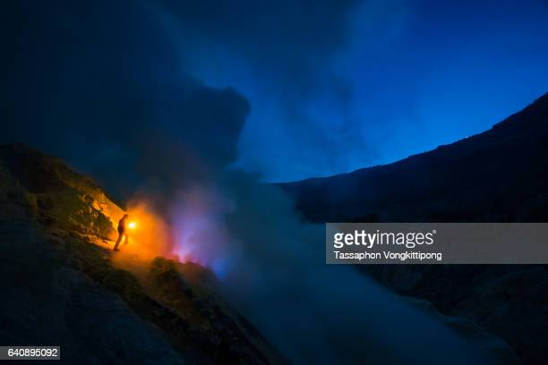 sulfur mine worker holding burning torch front of blue flame from burning sulfur