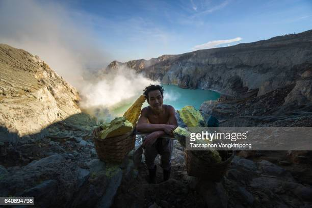 sulfur mine worker standing front of kawah ijen volcano crater with his baskets - sulfuric acid stock photos and pictures