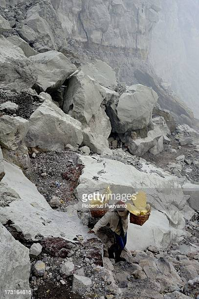 A sulfur miner carries two baskets of sulfur on July 9 2013 in Arjuna Java Indonesia Ijen Crater which is known as Kawah Ijen is located in the Ijen...