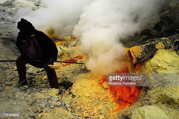 A sulfur miner tries to break sulfur chunks from a pipe flowing into Ijen Crater on July 9 2013 in Arjuna Java Indonesia Ijen Crater which is known...