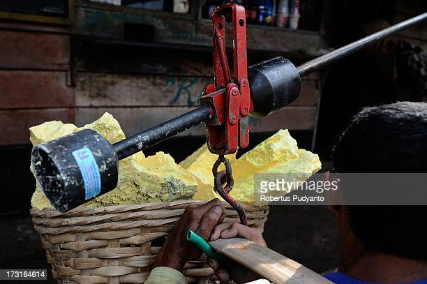 A sulfur miner weighs sulfur at the weighing station near Ijen Crater on July 9 2013 in Arjuna Java Indonesia Ijen Crater which is known as Kawah...