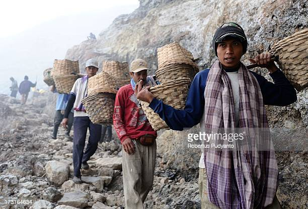 Sulfur miners carry empty baskets back down the slope on July 9 2013 in Arjuna Java Indonesia Ijen Crater which is known as Kawah Ijen is located in...