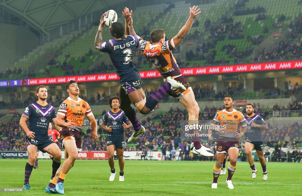 Suliasi Vunivalu of the Melbourne Storm beats Corey Oates of the Broncos to catch a high ball and then scores a try during the round 14 NRL match between the Melbourne Storm and the Brisbane Broncos at AAMI Park on June 10, 2018 in Melbourne, Australia.