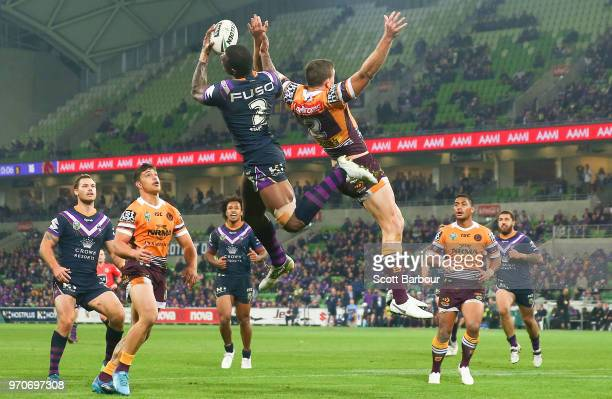 Suliasi Vunivalu of the Melbourne Storm beats Corey Oates of the Broncos to catch a high ball and then scores a try during the round 14 NRL match...