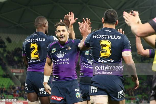 Suliasi Vunivalu of the Storm is congratulated by Billy Slater and his teammates after scoring a try during the round 13 NRL match between the...