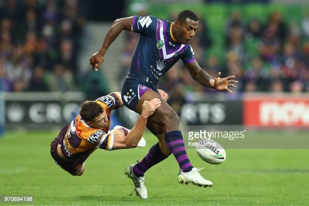 Suliasi Vunivalu of the Storm is is tackled by Corey Oates of the Broncos as he kicks the ball during the round 14 NRL match between the Melbourne...