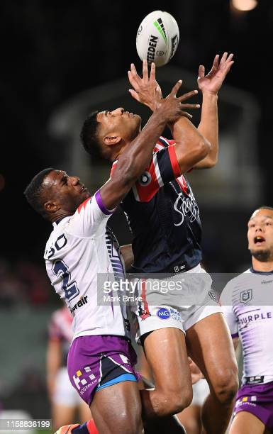 Suliasi Vunivalu of the Storm spoils and Daniel Tupou of the Roosters catch during the round 15 NRL match between the Sydney Roosters and the...