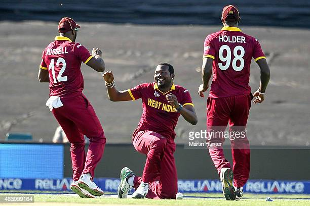 Sulieman Benn celebrates with Andre Russell and Jason Holder of West Indies during the 2015 ICC Cricket World Cup match between Pakistan and the West...