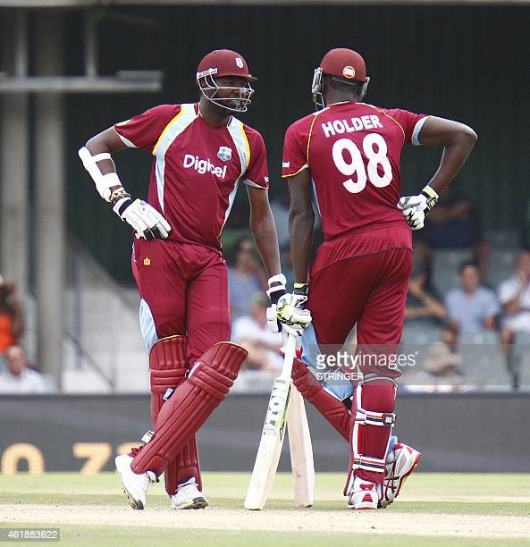 Sulieman Benn of the West Indies and teammate Jason Holder look on during the third One Day International at the East London cricket ground in East...