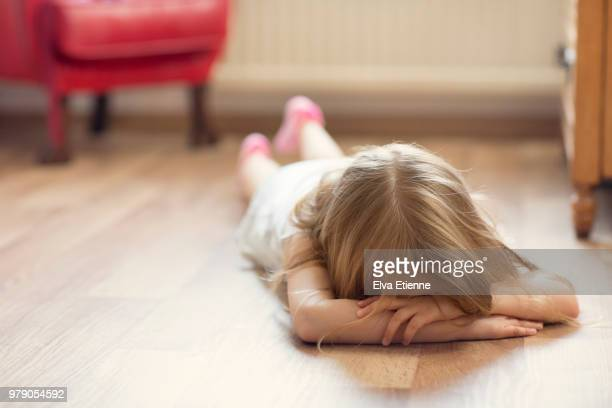 Sulking girl lying on floor with head in hands