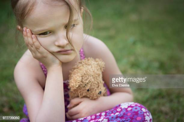 Sulking girl sitting with head in hands, outdoors with teddy bear