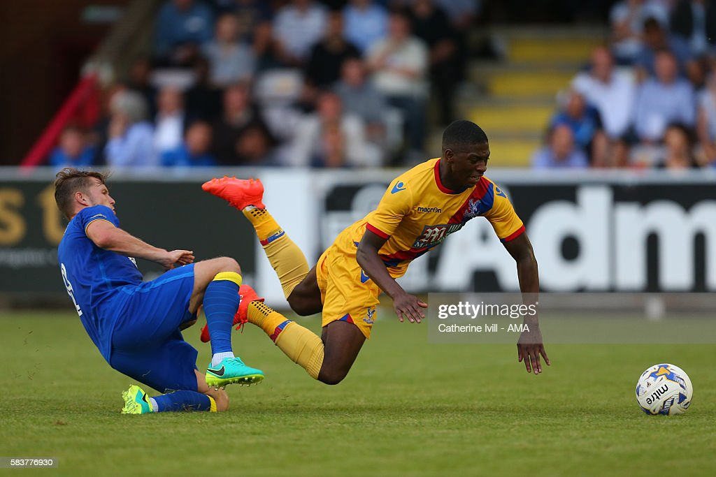 Sullay Kaikai of Crystal Palace is tackled by Jake Reeves of AFC Wimbledon during the Pre-Season Friendly match between AFC Wimbledon and Crystal Palace at The Cherry Red Records Stadium on July 27, 2016 in Kingston upon Thames, England.