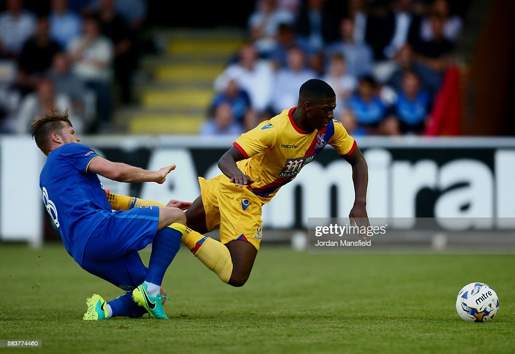 Sullay Kaikal of Crystal Palace is taken down by Jake Reeves of AFC Wimbledon during the pre-season friendly between AFC Wimbledon and Crystal Palace at The Cherry Red Records Stadium on July 27, 2016 in Kingston upon Thames, England.