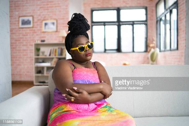 sullen african woman sitting arms crossed on sofa - flat chested woman stock photos and pictures