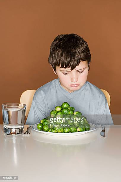 Sullen boy with a plate of Brussels sprouts