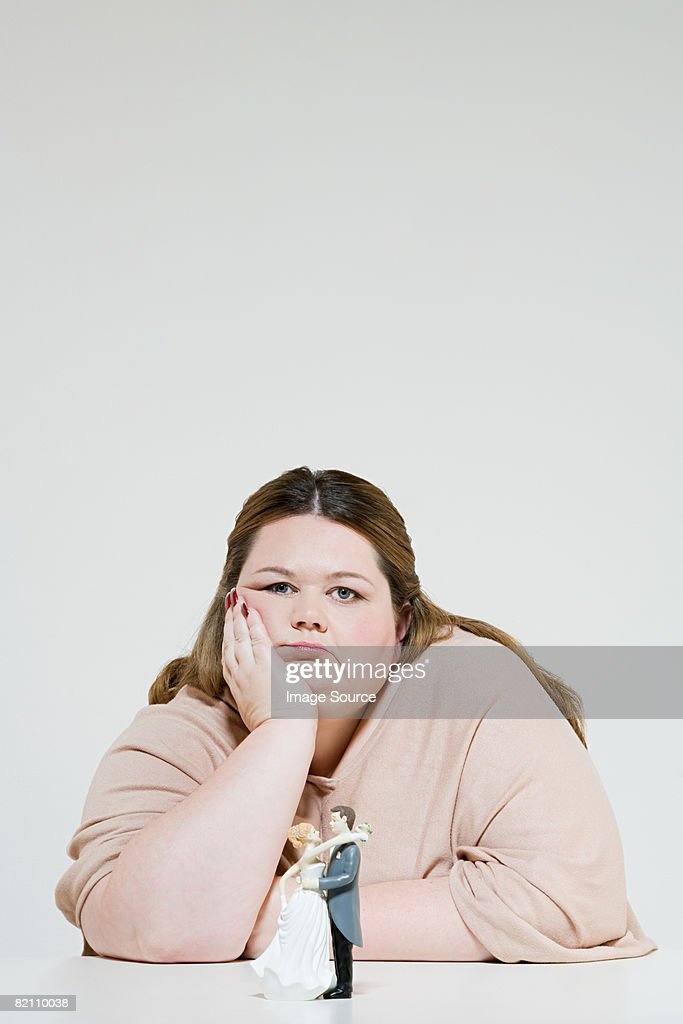 Sullen woman with wedding figurines : Stock Photo