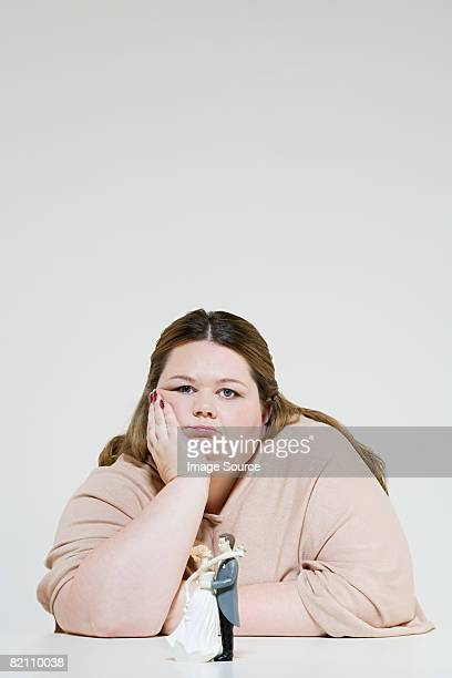 Sullen woman with wedding figurines
