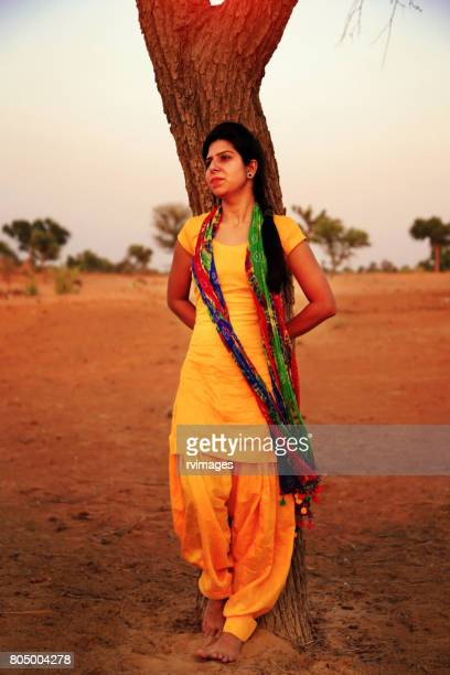 sullen women near the tree trunk in desert - salwar kameez stock pictures, royalty-free photos & images