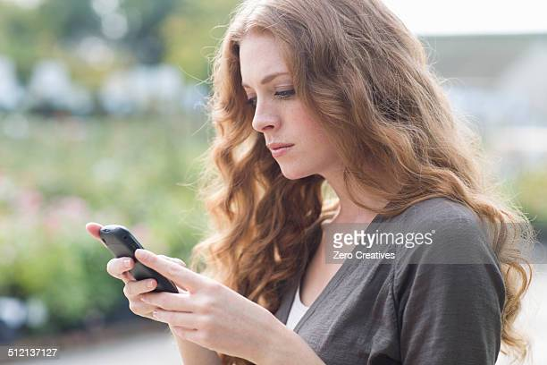Sullen young woman reading texts on smartphone in garden