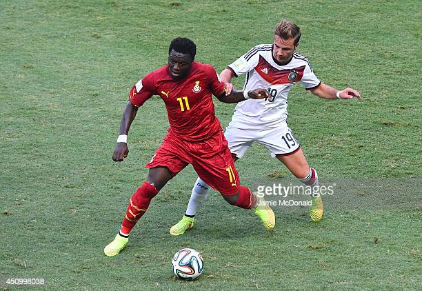 Sulley Muntari of Ghana and Mario Goetze of Germany compete for the ball during the 2014 FIFA World Cup Brazil Group G match between Germany and...
