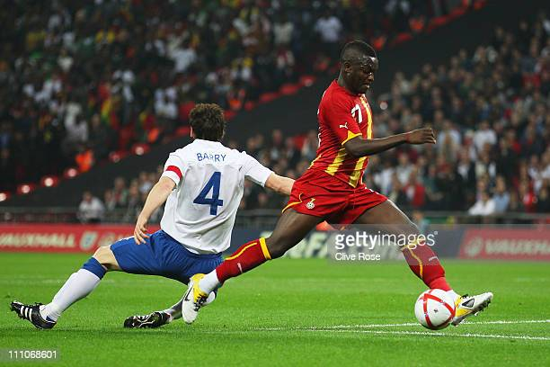 Sulley Muntari of Ghana is challenged by Gareth Barry of England during the international friendly match between England and Ghana at Wembley Stadium...