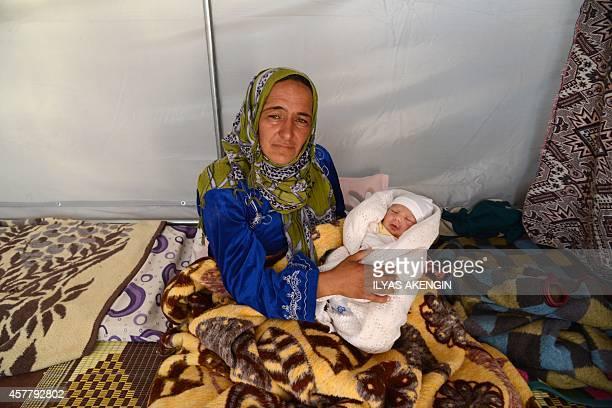 Sultan Muslim poses with her newborn son Muhammed Obama Muslim at Suruc Rojava refugee camp in Sanliurfa on October 22 2014 Muslim a Syrian Kurdish...