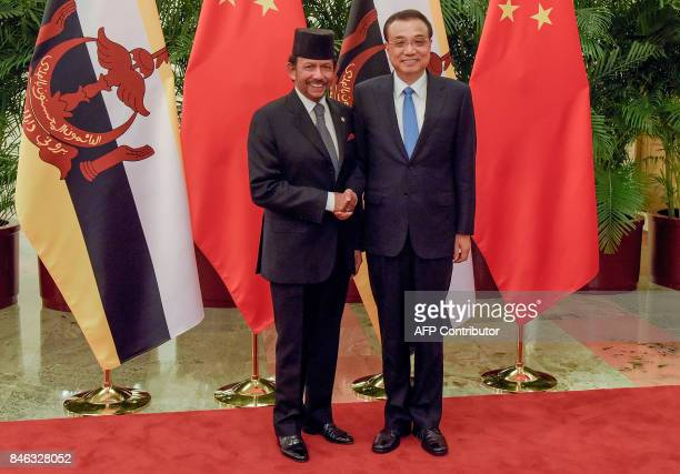 Sultan of Brunei Hassanal Bolkiah shakes hands with Chinese Premier Li Keqiang prior to their meeting at the Great Hall of the People in Beijing on...