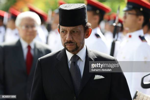 Sultan of Brunei Hassanal Bolkiah walks back after inspecyting the guard of honour accompanied by Singapore President Tony Tan Keng Yam during the...