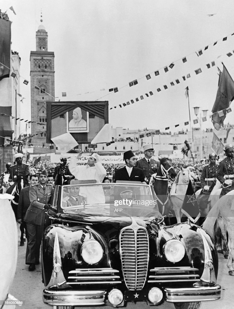 Sultan of Morocco Muhammad ibn Yusuf (L), standing in car, is greeted by the crowd at his arrival in Casablanca, with his son Prince Moulay Hassan (L), and his aide-de-camp Mohamed Oufkir (in front of the car, L), on February 09, 1956 in Casablanca. Mohammed V returned from exile on 16 November 1955, and in February 1956, successfully negotiated with France for the independence of Morocco. / AFP / -