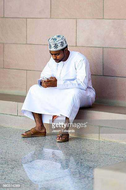 a muslim man in a dishdasha and kuma texting on his mobile phone at the grand mosque. - oman stock pictures, royalty-free photos & images
