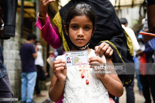 Suma Akhtar displays a picture of her mother who went missing after the fire broke out in a factory, outside the Dhaka Medical College and Hospital...