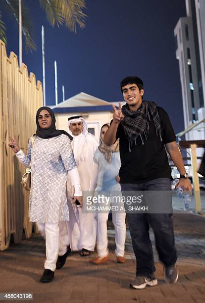 Sumaya Rajab wife of jailed Bahraini human rights activist Nabeel Rajab and her son Adam Rajab flash the sign of victory as they leave the Bahrain...