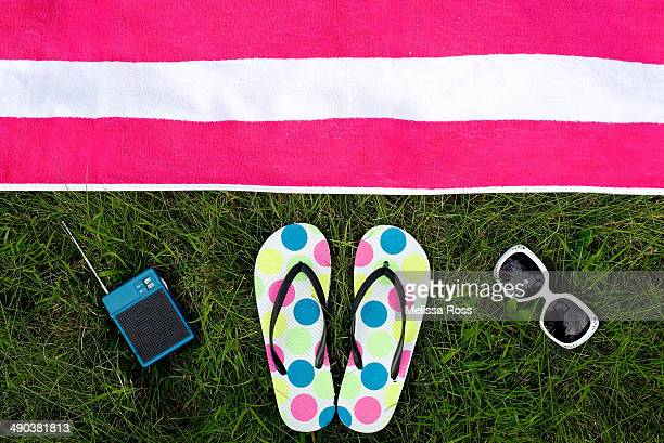 Summer accessories placed next to a beach towel