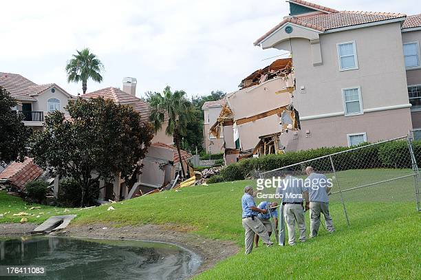 Summer Bay Resort employees install barricades around the collapsed building by a sinkhole at Summer Bay Resort near Walt Disney World on August 12...