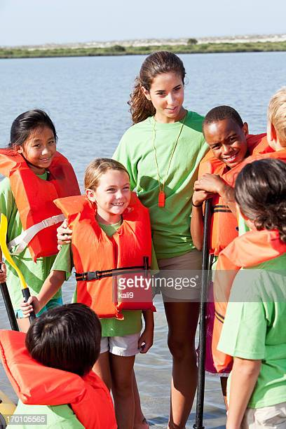 Summer camp counselor and children with kayak