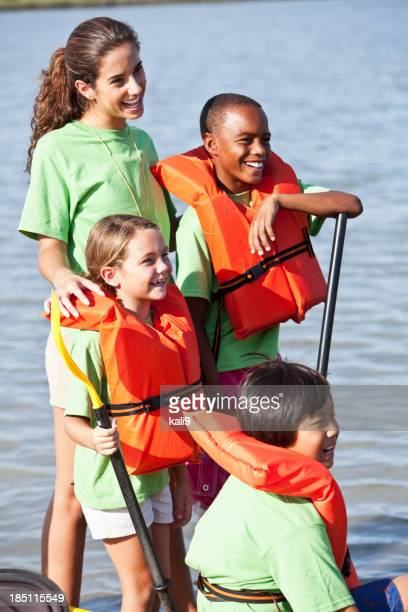Summer camp counselor with children and kayak