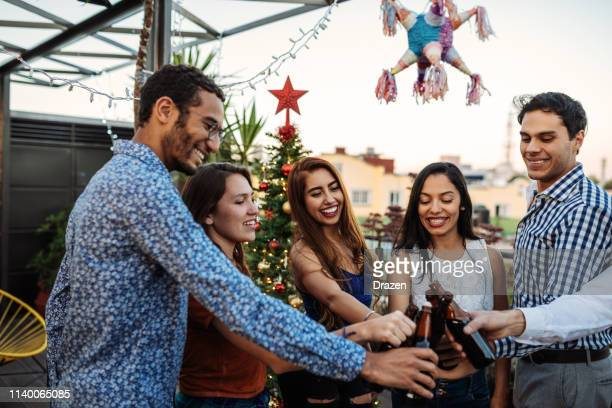 summer christmas party on rooftop - diverse latino friends celebrating christmas together - mexican beer stock pictures, royalty-free photos & images