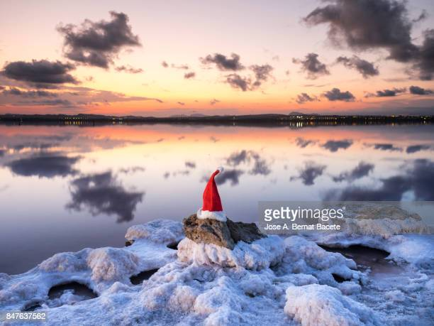 Summer Christmas, Santa Claus Christmas hat on a rock on the shore of a salt lake at sunset.