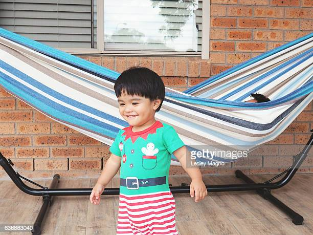 Summer Christmas - toddler is in front of hammock while his dad is sleeping