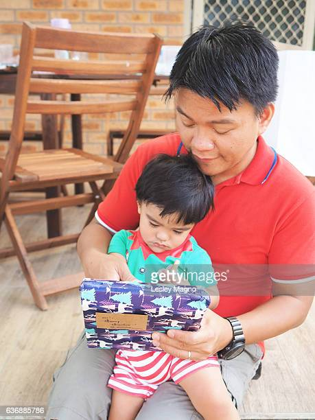 Summer Christmas - toddler opening gifts with his dad