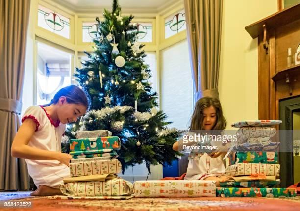 Summer Christmas: young sibling girls opening presents, Xmas tree
